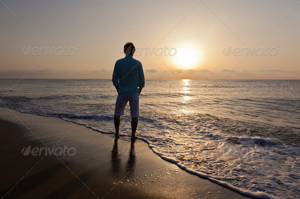 Alone caucasian man standing on beach watching the sunrise. - Stock Photo - Images