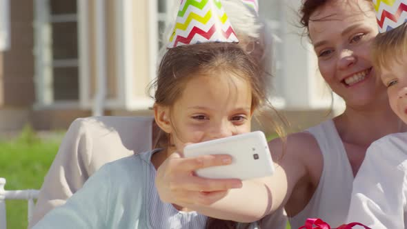 Woman Taking Selfie with Kids and Grandmother on Outdoor Party