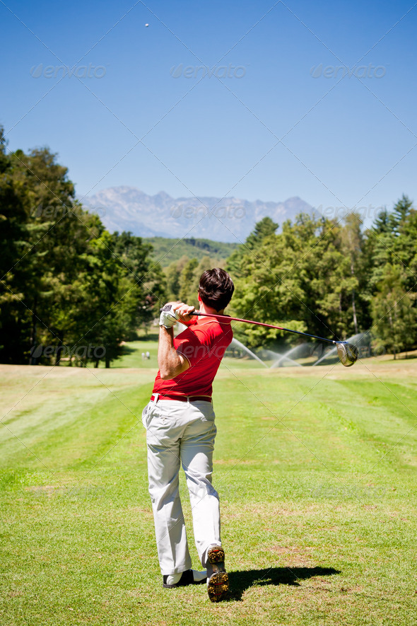 Golf player performs a tee shot using a driver club. - Stock Photo - Images