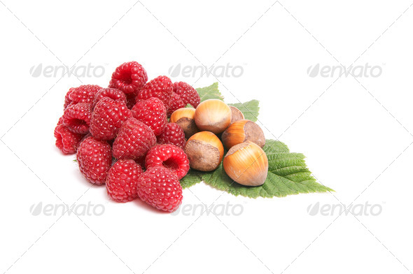 Juicy raspberries and nuts on a white. - Stock Photo - Images