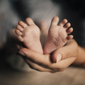 mother hold feets newborn baby