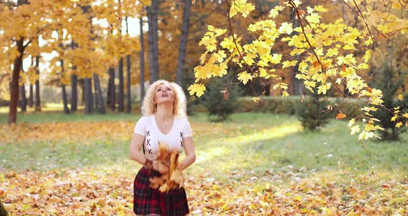 Happy Blonde Woman in Sexy Crop Top and Skirt Playing with Foliage in Park