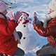 Happy Girls Playing a Game in Front of a Snowman - VideoHive Item for Sale