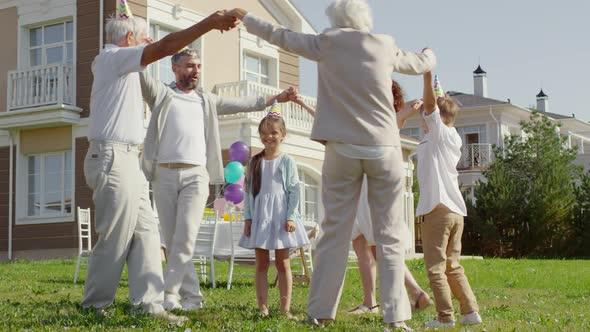 Happy Family Dancing around Little Birthday Girl Outdoors