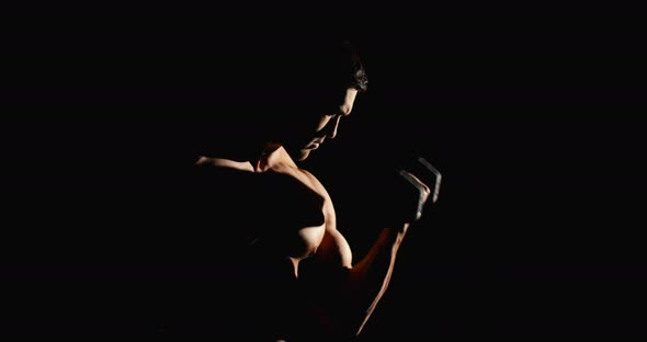Athletic Man Working Out With Dunbbells In Gym Black Background