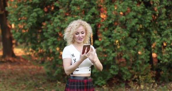 Blonde in Looking at Phone, Getting Message and Laughing