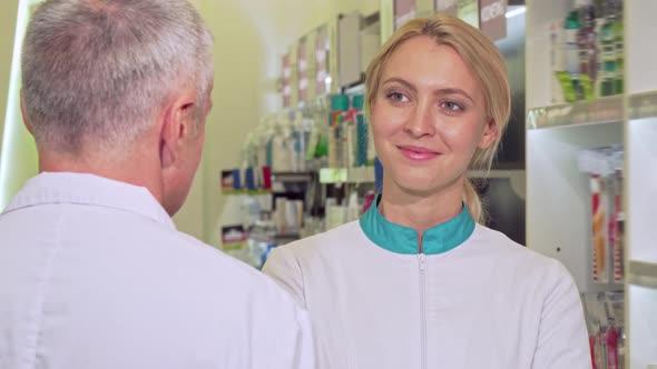 Lovely Female Chemist Smiling Joyfully, Talking To Her Senior Colleague