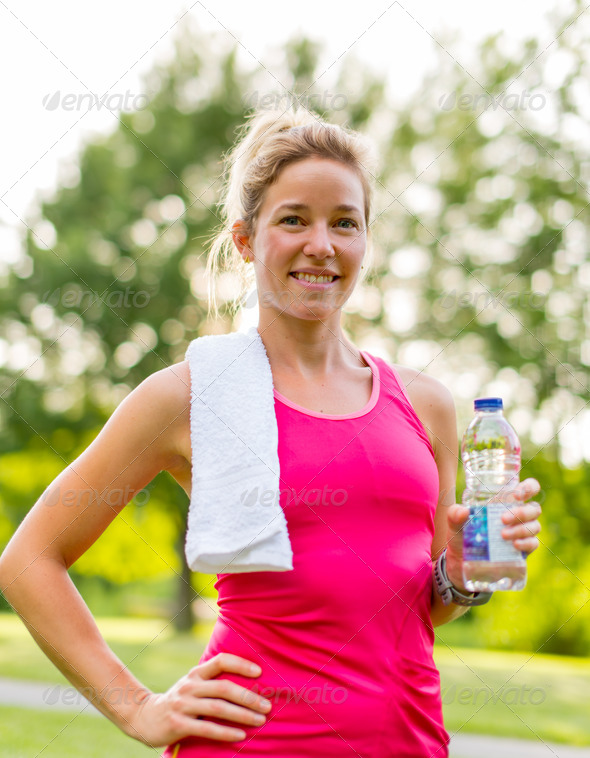 blond woman with a water bottle and towel - Stock Photo - Images