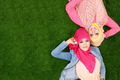 Two beautiful happy muslim woman smiling lying on grass with cop