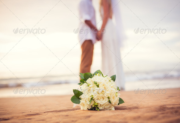 Just married couple holding hands on the beach - Stock Photo - Images