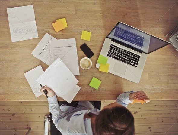 Overhead view of businesswoman working at desk - Stock Photo - Images