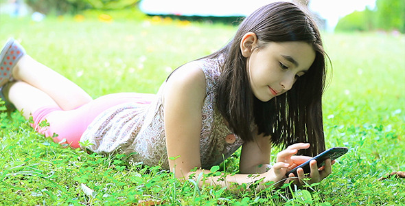little girl playing video games on smartphone by marianst