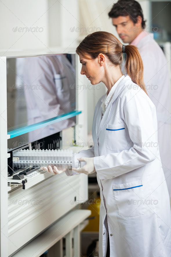 Researcher Loading Samples In Analyzer - Stock Photo - Images