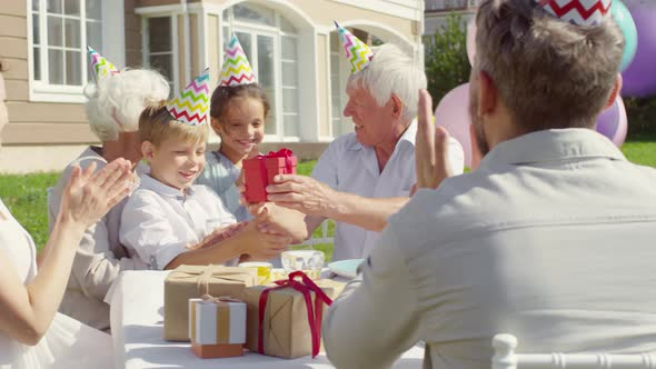 Grandfather Receiving Birthday Gift from Family on Outdoor Party