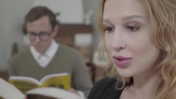 Beautiful Blond Woman Reading Aloud the Book in the Foreground While Modestly
