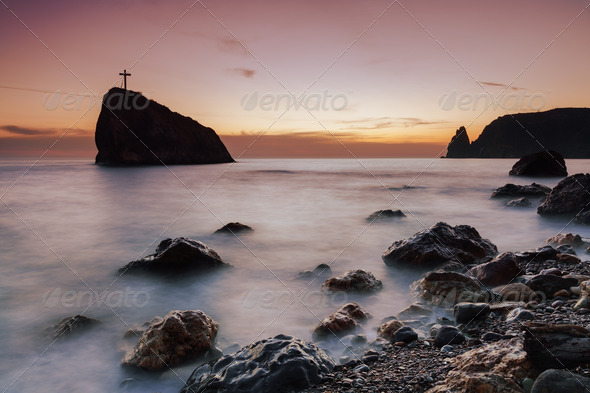 Seacoast at sunset and a cross on a rock - Stock Photo - Images