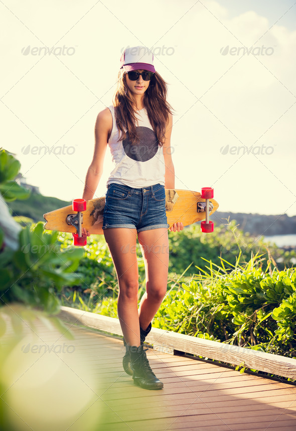 Beautiful young woman with a skateboard - Stock Photo - Images