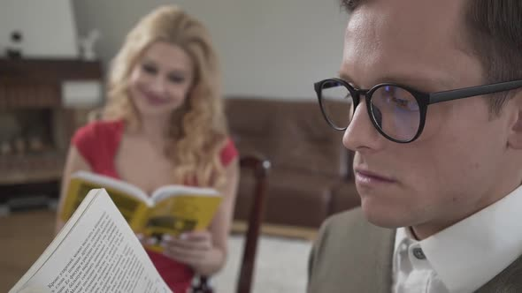 Young Modestly Dressed Man in Glasses Reading the Book in the Foreground While Curly Blond Woman