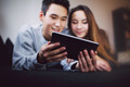 Teenage couple using tablet PC at home
