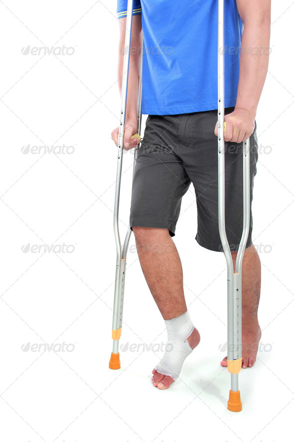 portrait of a broken foot using crutch - Stock Photo - Images