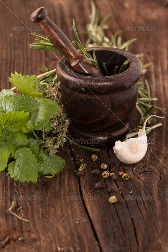 garlic and herbs in mortar - Stock Photo - Images