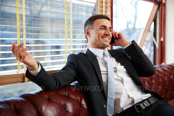 Happy businessman sitting and talking on the phone at office - Stock Photo - Images