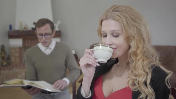 Beautiful Blond Woman Drinking Coffee in the Foreground While Modestly Dressed Man Reading the Book