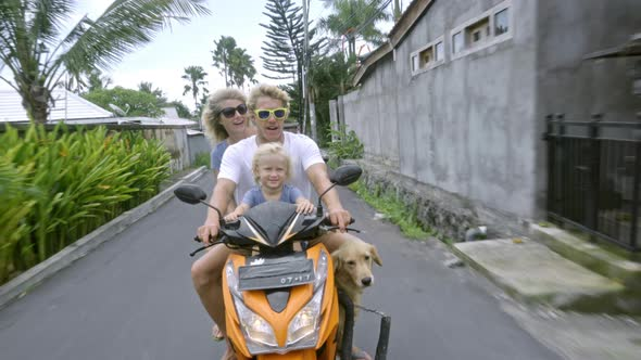 Joyful Family Riding on Scooter with Dog
