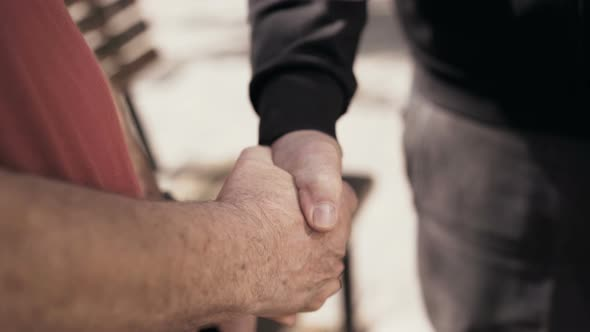 Handshaking of Two Aged Lonely Seniors Meeting on a Street