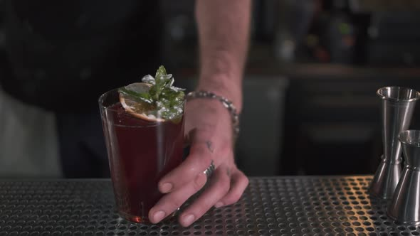 Fresh Cocktail Decorated with Mint and Orange Standing on Bar Counter
