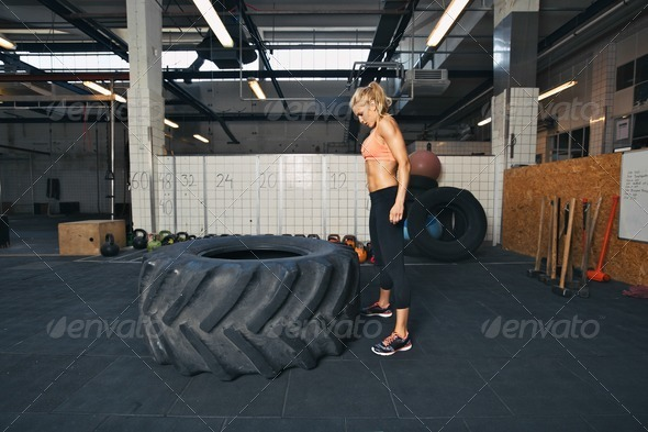 Female athlete performing tire flipping crossfit exercise - Stock Photo - Images