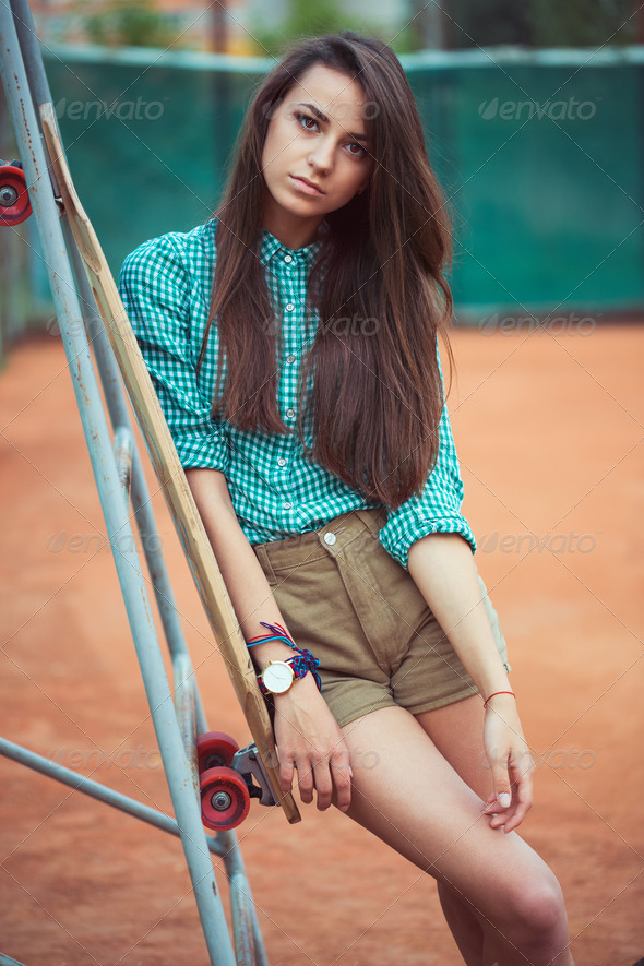Beautiful young girl with longboard standing on the tennis court - Stock Photo - Images