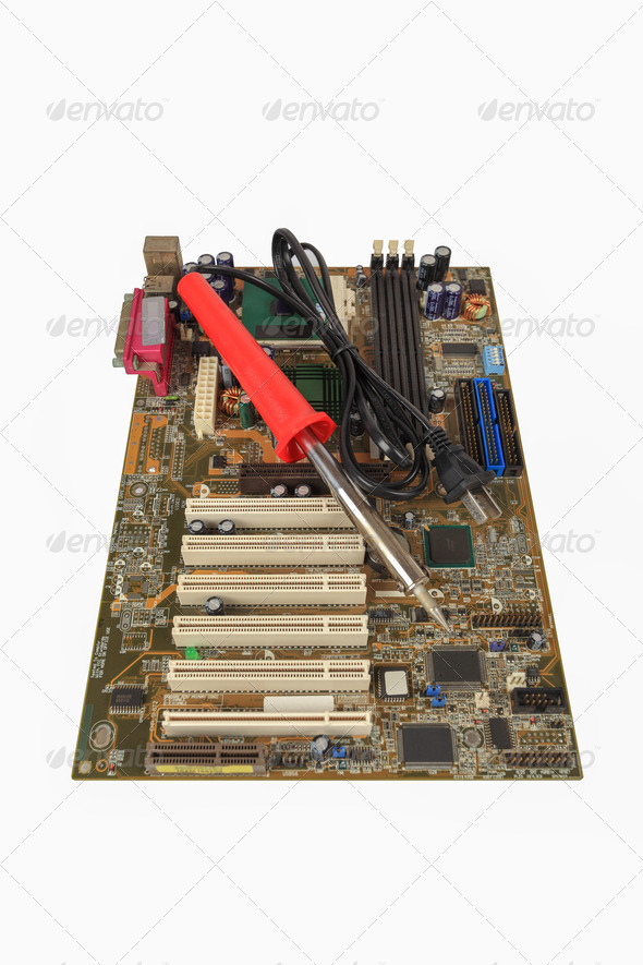 soldering iron and computer motherboard - Stock Photo - Images