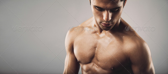 Portrait of fit masculine man looking down - Stock Photo - Images