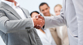 Businessmen shaking hand in front of their colleagues - PhotoDune Item for Sale