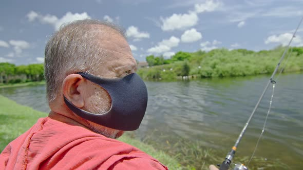 Slow Motion of Elderly Man Wearing Face Mask While Fishing on a Lake by  sevillagroupstudio
