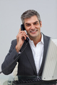 Smiling mature male executive talking on phone