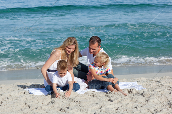 Happy family playing on the sand - Stock Photo - Images