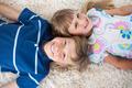 Siblings lying on the floor