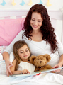 Mother and daughter reading in bed