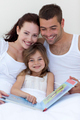 Parents and daughter reading in bed