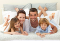 Happy family lying in bed and smiling at the camera - PhotoDune Item for Sale