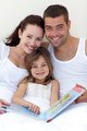 Portrait of parents and daughter reading in bed