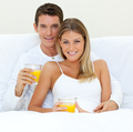 Happy couple drinking orange juice lying on their bed