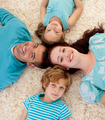 Happy family on floor with heads together - PhotoDune Item for Sale