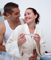 Happy couple in bathroom holding a pregnancy test