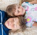Siblings sleeping on the floor