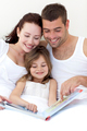 Young family reading in bed