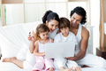 Family using a laptop on the sofa - PhotoDune Item for Sale
