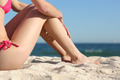 Sunbather woman legs sitting on the sand of the beach - PhotoDune Item for Sale